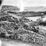 W-Beach těsně před finální evakuací v lednu 1916, v pozadí zřetelný útes, z kterého Turci masakrovali vyloďujíci se Angličany